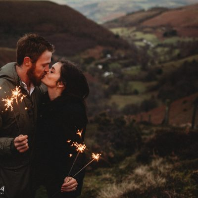 North Wales Wedding Photographer - couple kissing with sparklers against stunning backdrop in North Wales