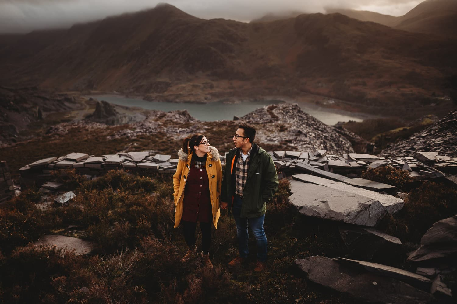 Engaged couple in Snowdonia overlooking the Snowdon mountain range and a lake and quarry