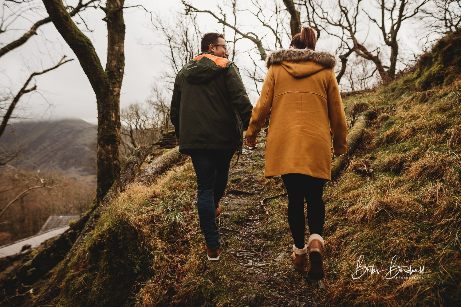 Engaged couple holding hands walking up a path into a forest