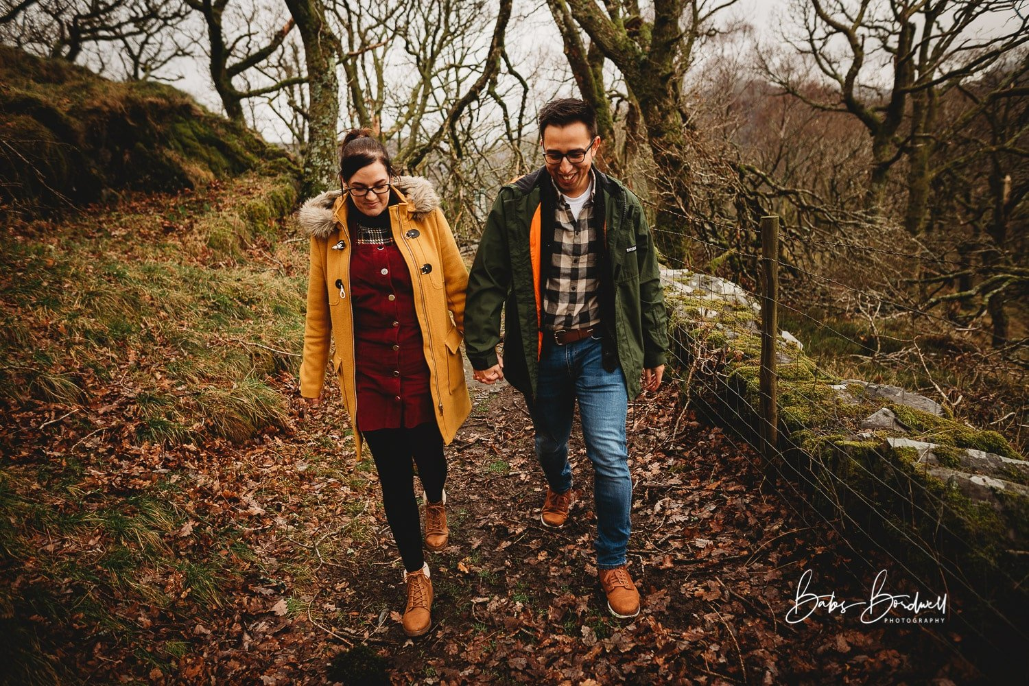 engaged couple walking on a forest path holding hands smiling