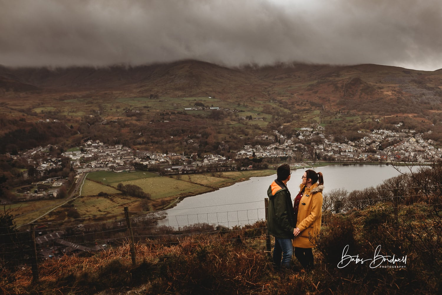 engaged couple facing each other holding hands overlooking Llanberis and Llyn Padarn with moody clouds in the background
