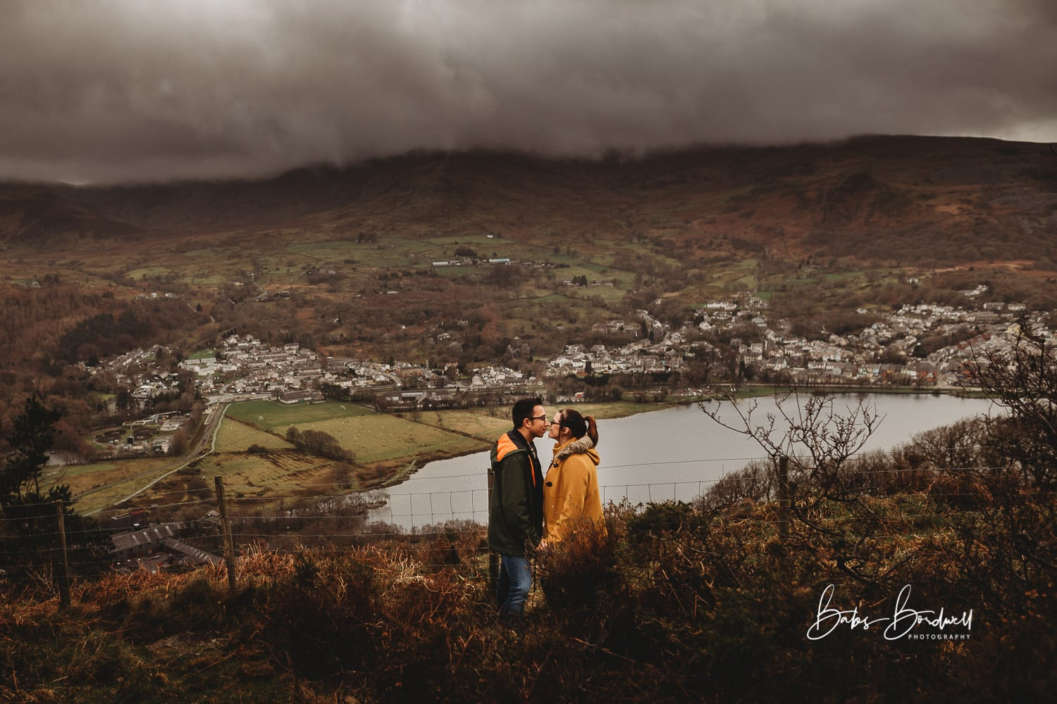 engaged couple facing each other kissing overlooking Llanberis and Llyn Padarn with moody clouds in the background