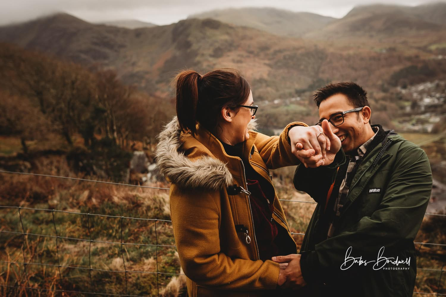 engaged couple laughing showing off her engagement ring against a mountain backdrop