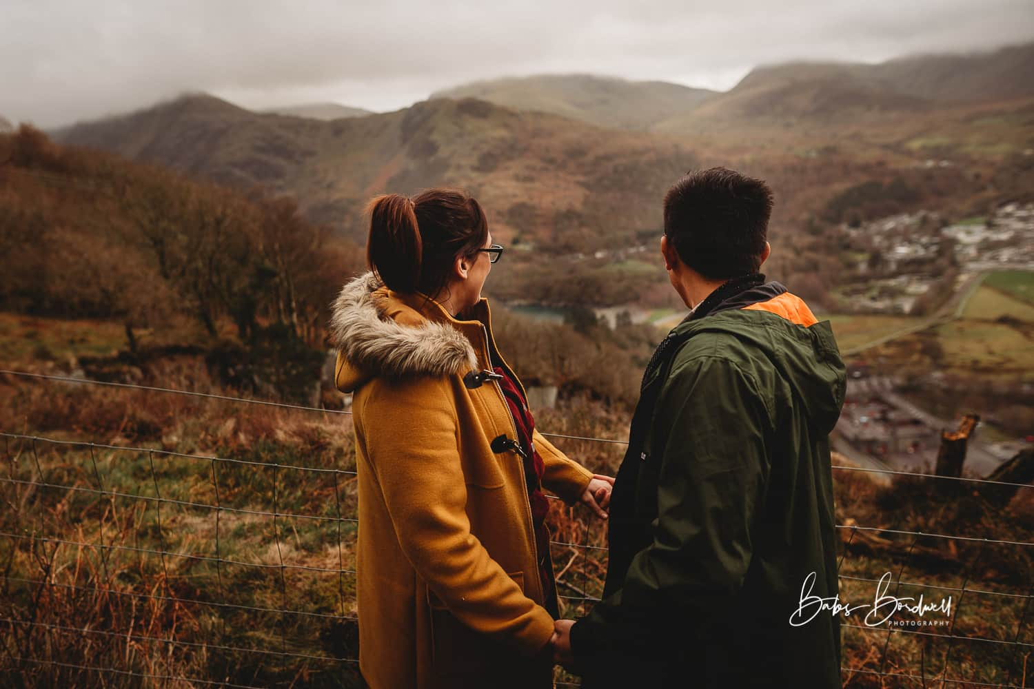 engaged couple holding hands looking across a Snowdonia mountain range