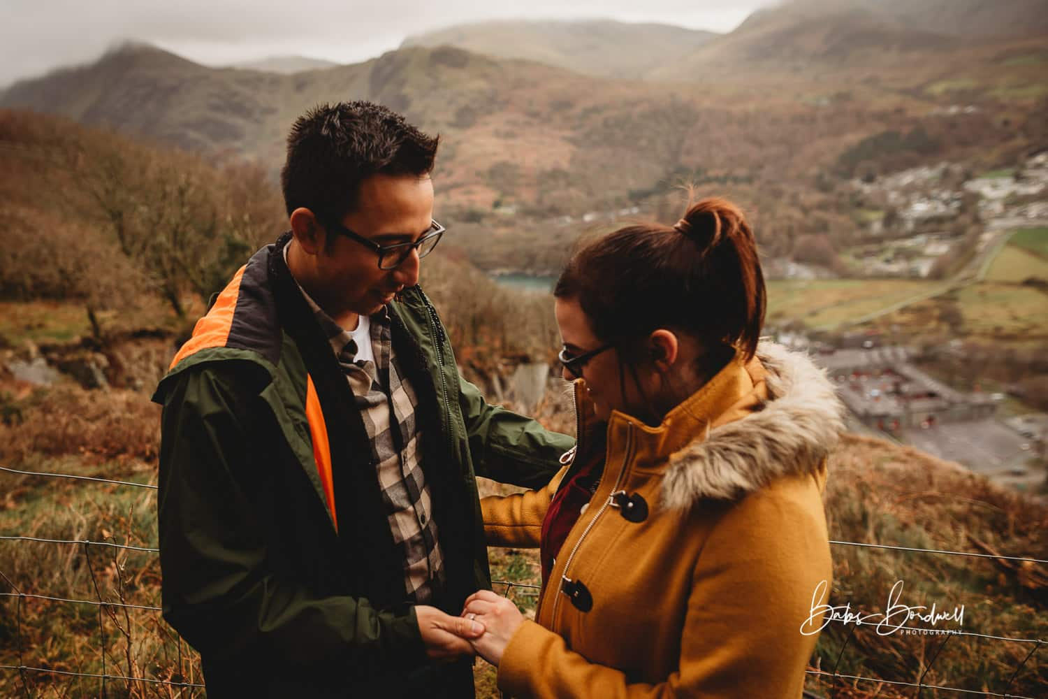 engaged couple looking at engagement ring on girl's hand against a mountainous Snowdonia backdrop