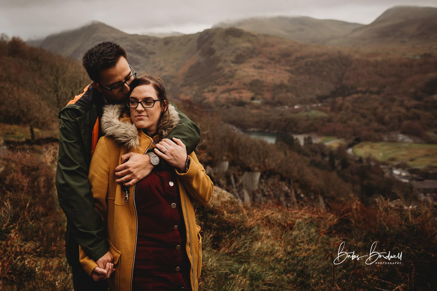 portrait of engaged couple hugging each other against a mountainous Snowdonia backdrop