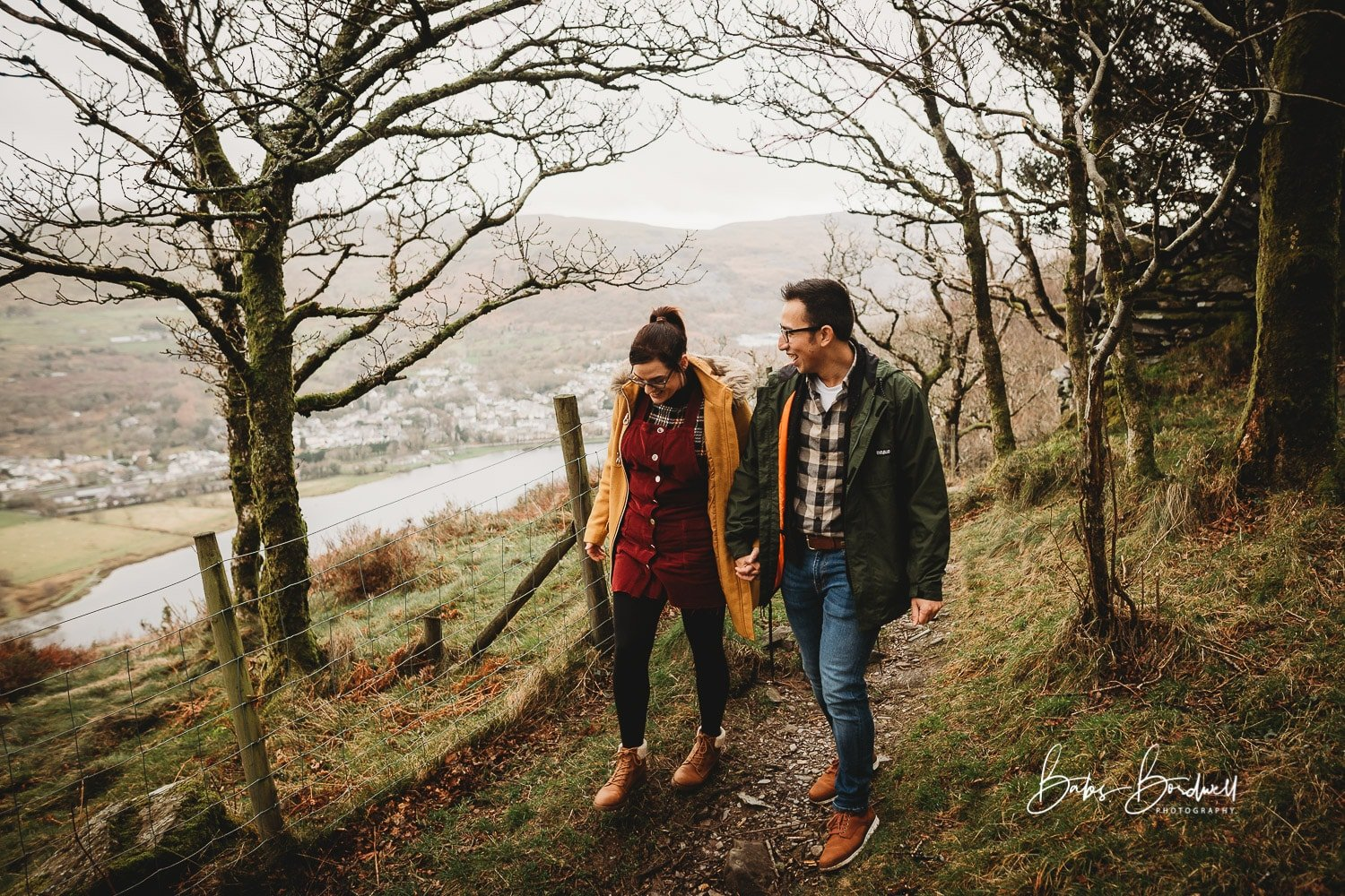engaged couple smiling walking on forest path above Llanberis