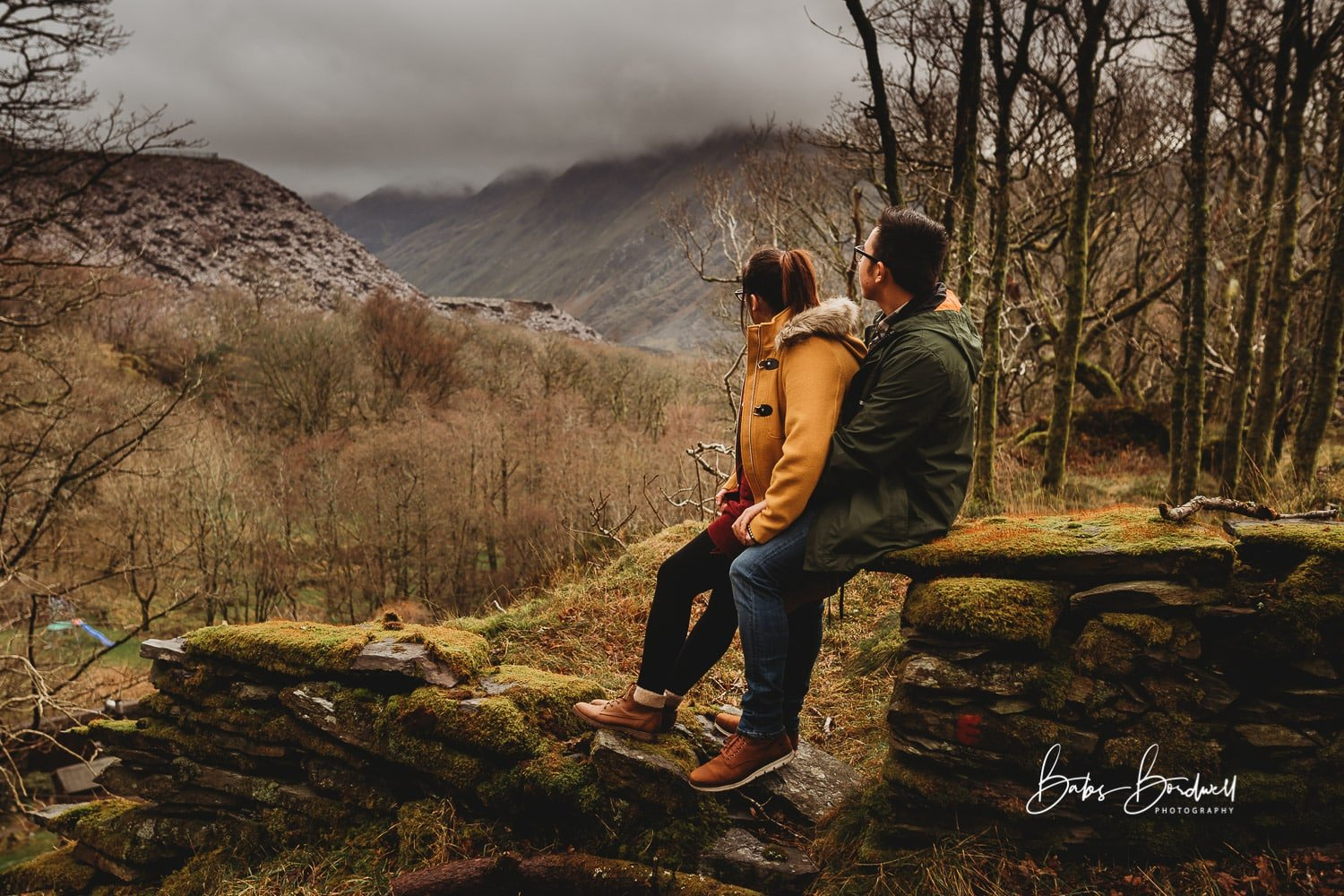 couple sitting on a stone wall with the woman in front looking towards the Snowdon mountain range