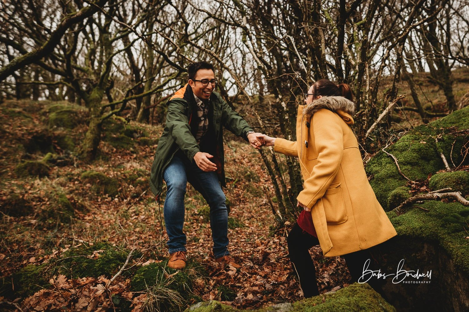 man helping his fiancee up a steep bit in a forest smiling
