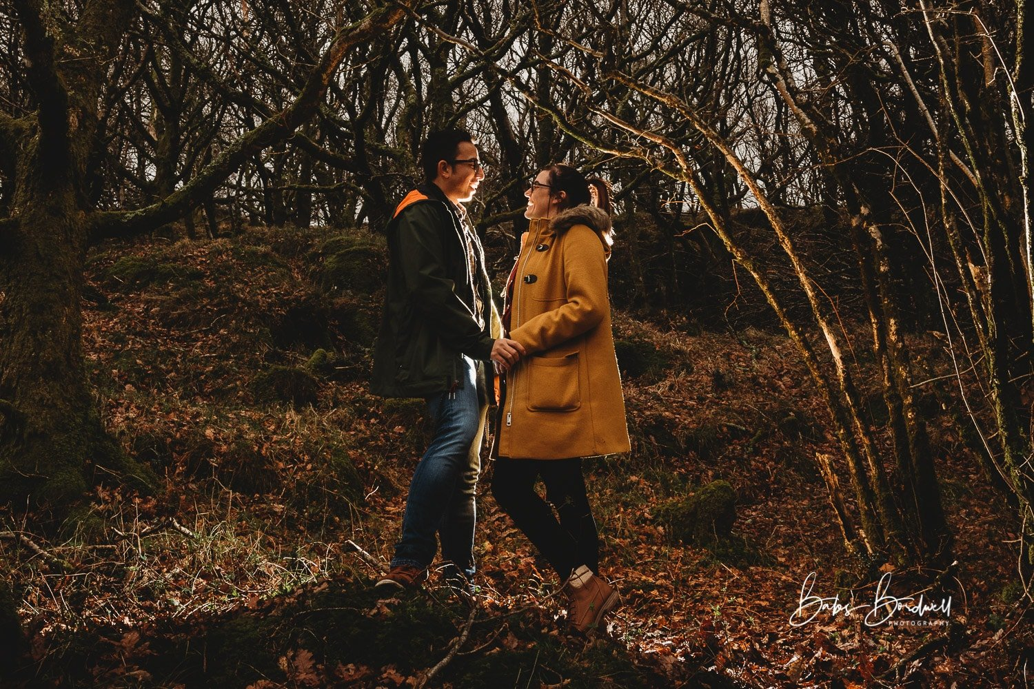 engaged couple in forest looking at each other and holding hands