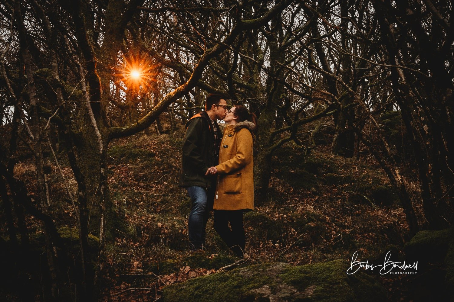 engaged couple kissing while holding hands in a forest