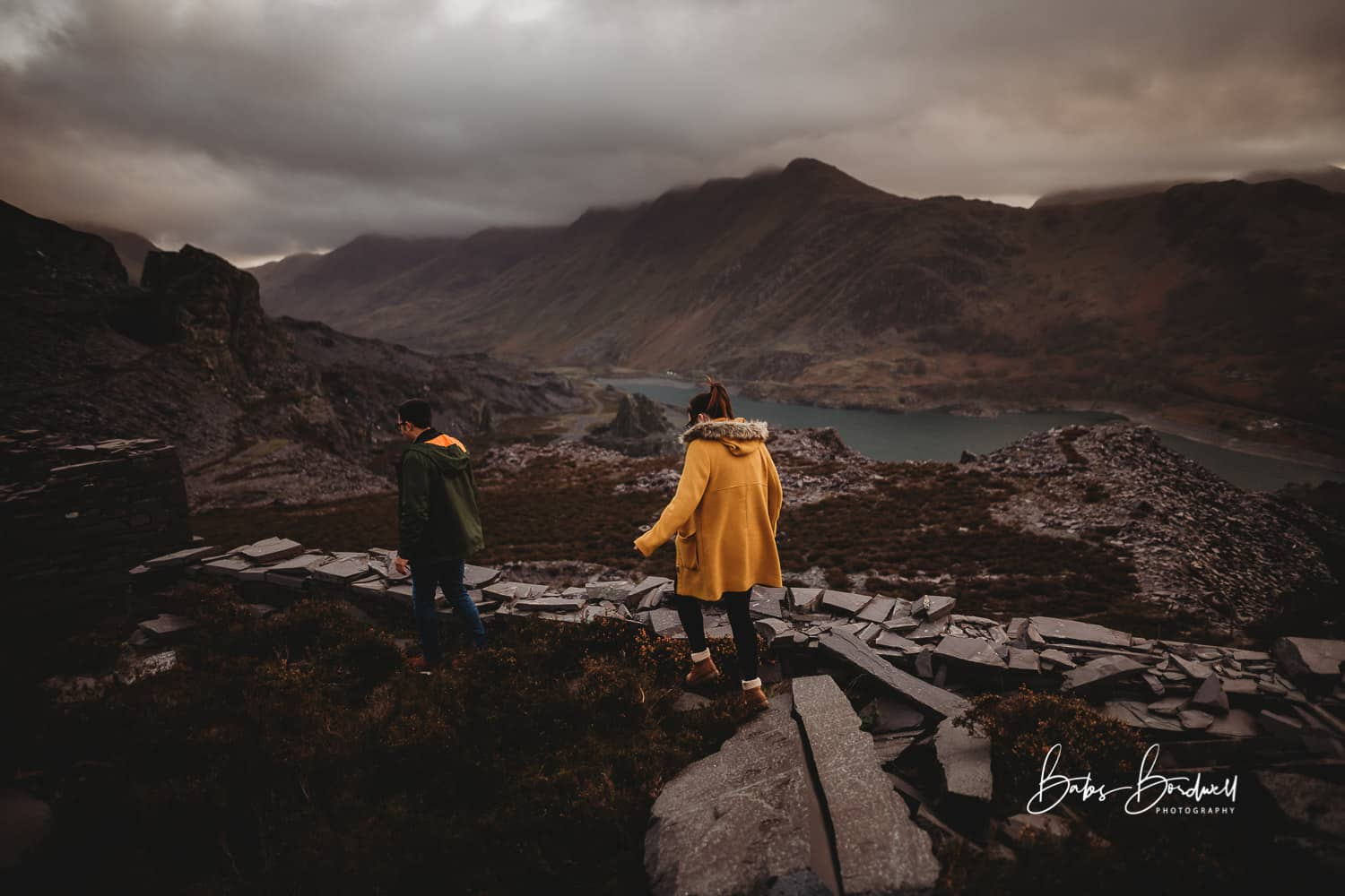 couple walking man in front of woman against a mountainous Snowdonia backdrop