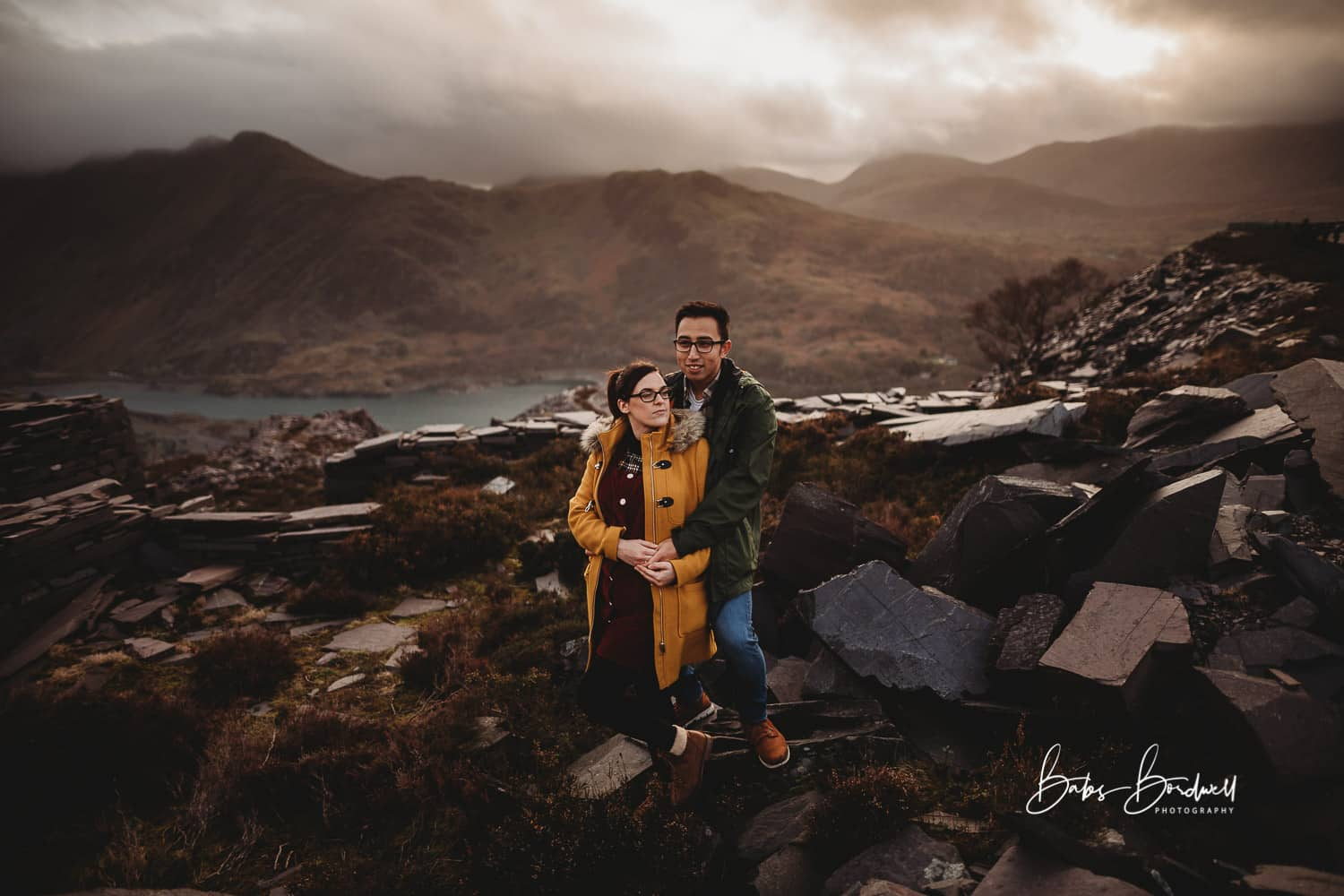couple looking at each other and holding hands against a mountainous Snowdonia backdrop