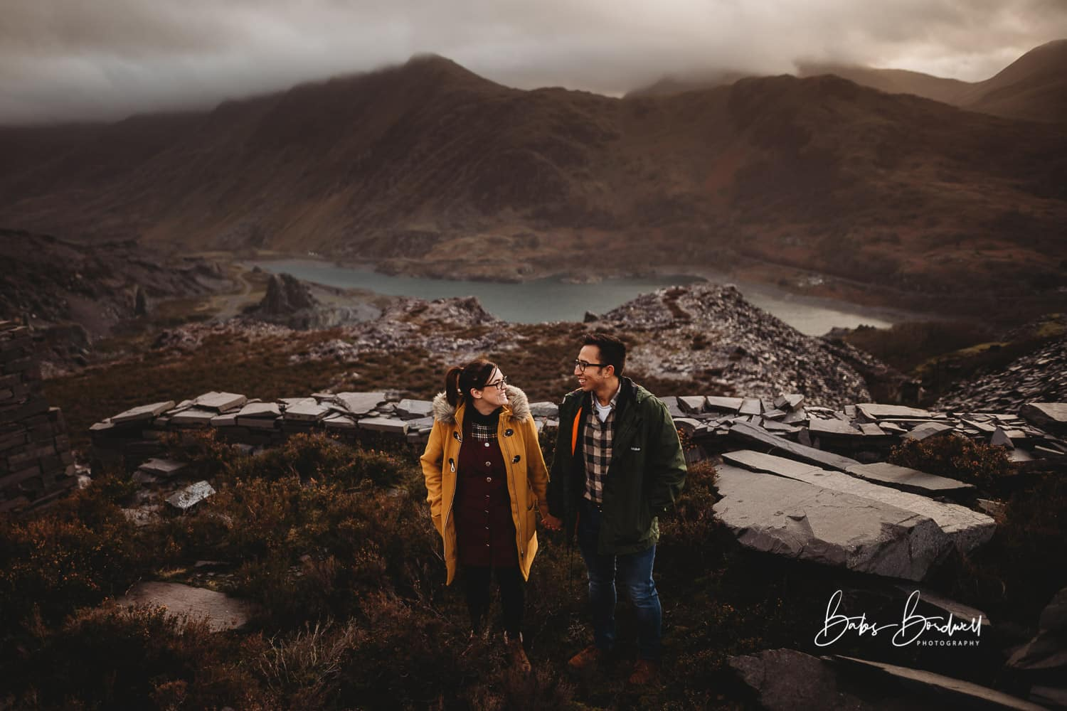 couple looking at each other while standing next to each other against a  mountainous Snowdonia backdrop