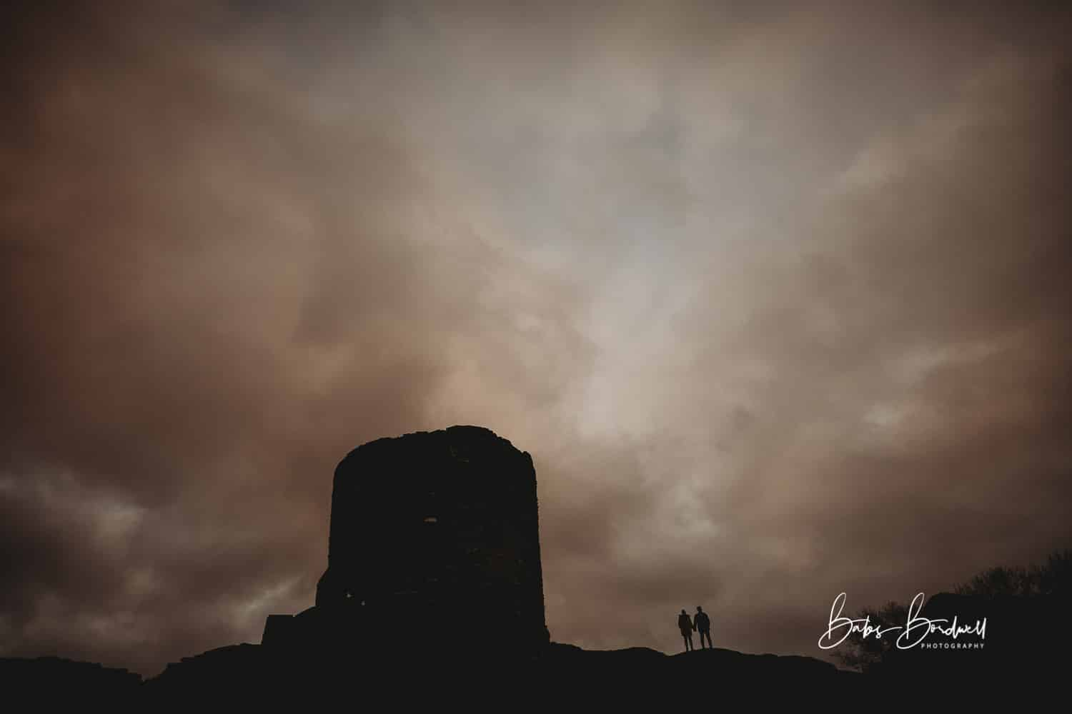 silhouette of couple next to castle with dramatic sky