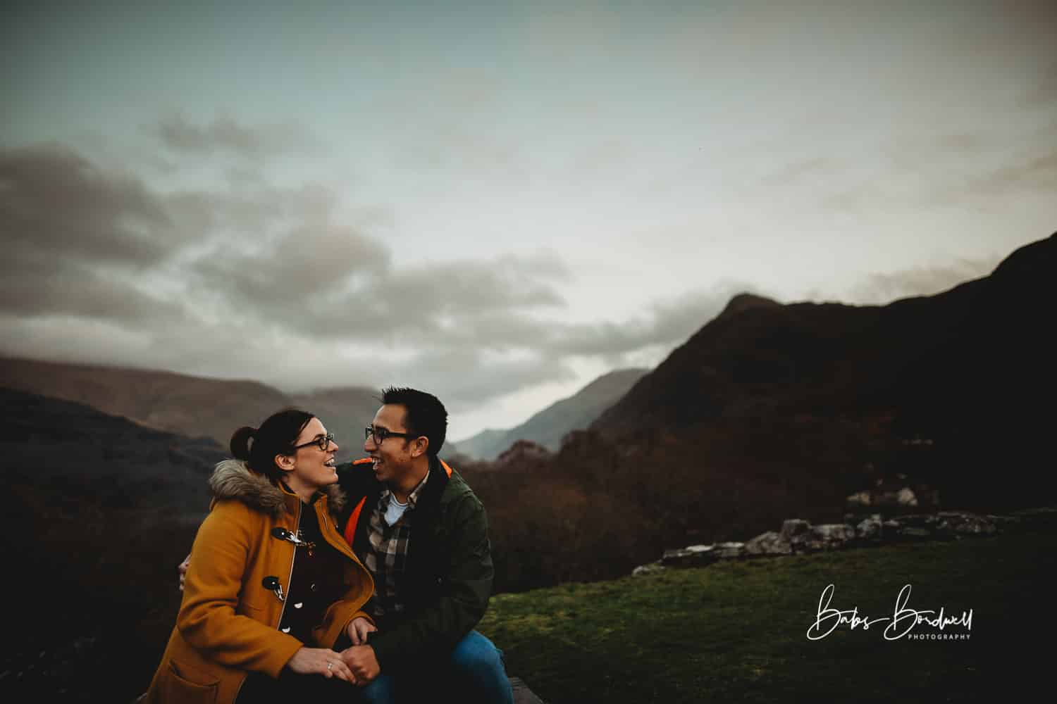 couple looking at each other while sitting down with his hands on her knee against mountainous Snowdonia backdrop