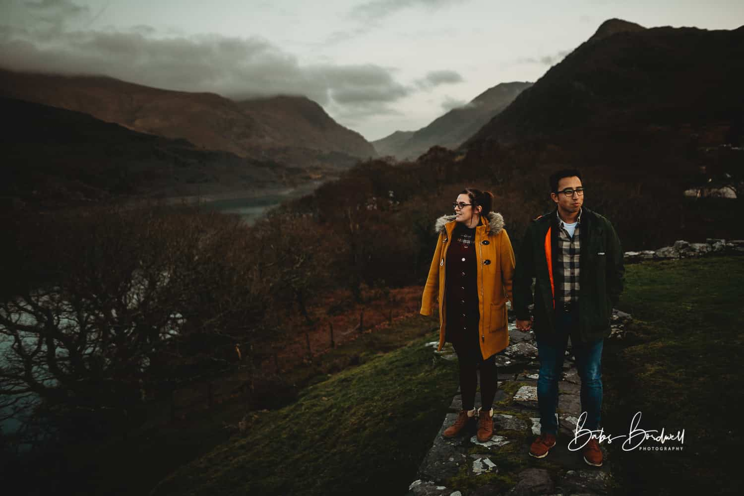 couple standing next to each other while holding hands against mountainous Snowdonia backdrop