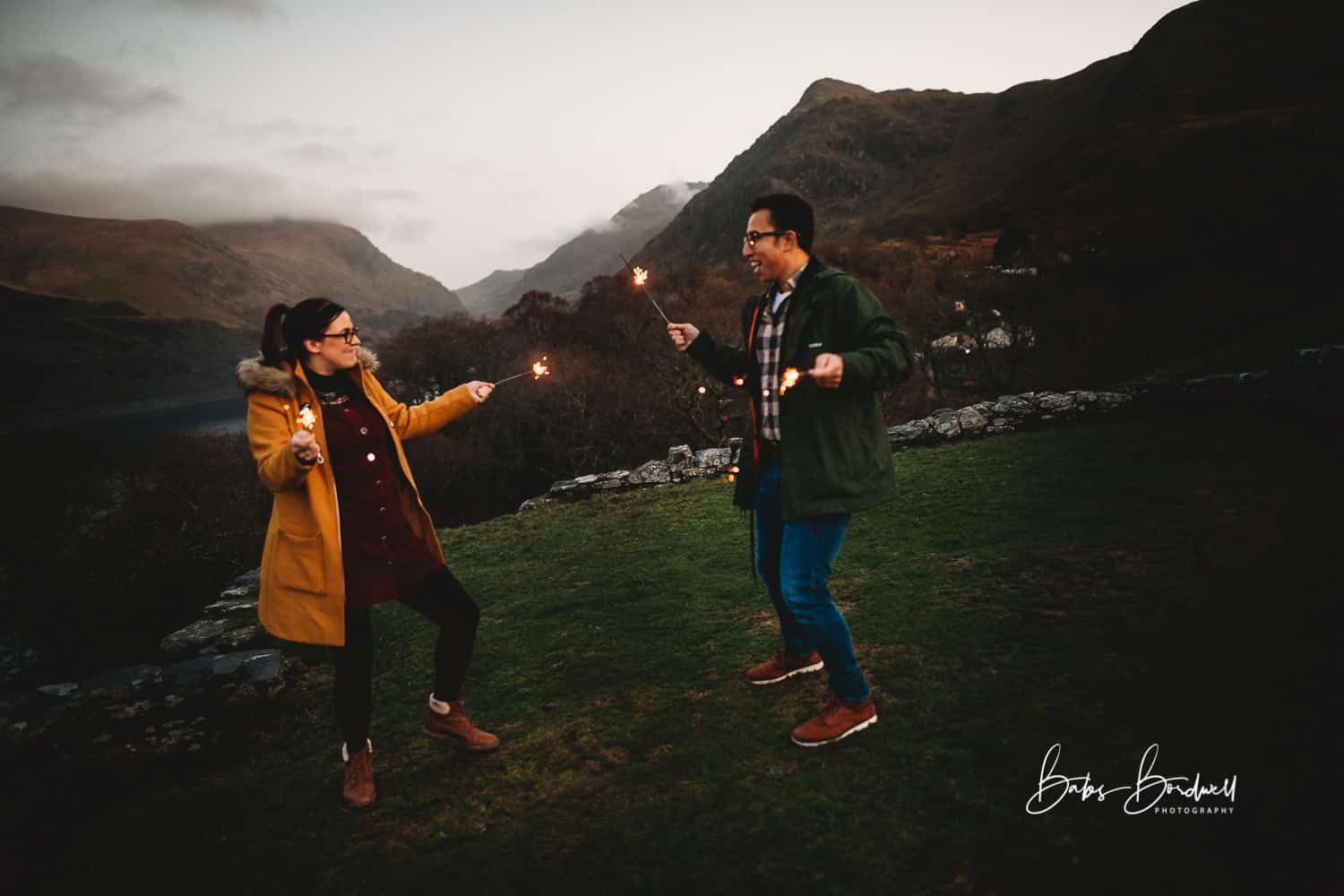 couple having fun with sparklers against a mountainous Snowdonia backdrop