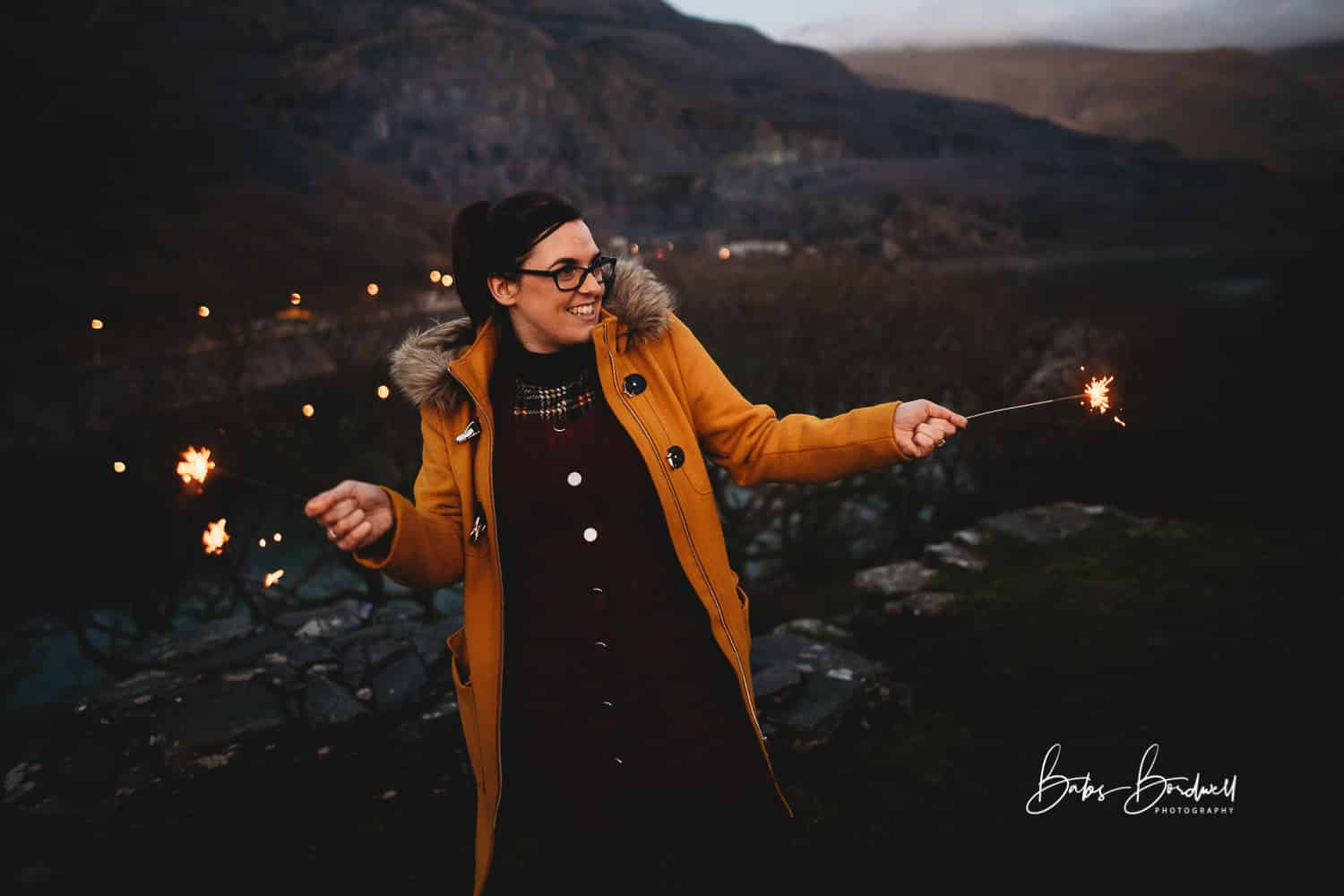 female having fun with sparklers against a mountainous Snowdonia backdrop