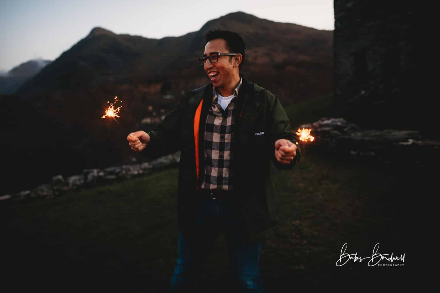 male having fun with sparklers against a mountainous Snowdonia backdrop
