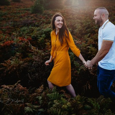 North Wales Wedding Photographer - engaged couple walking and smiling at one another