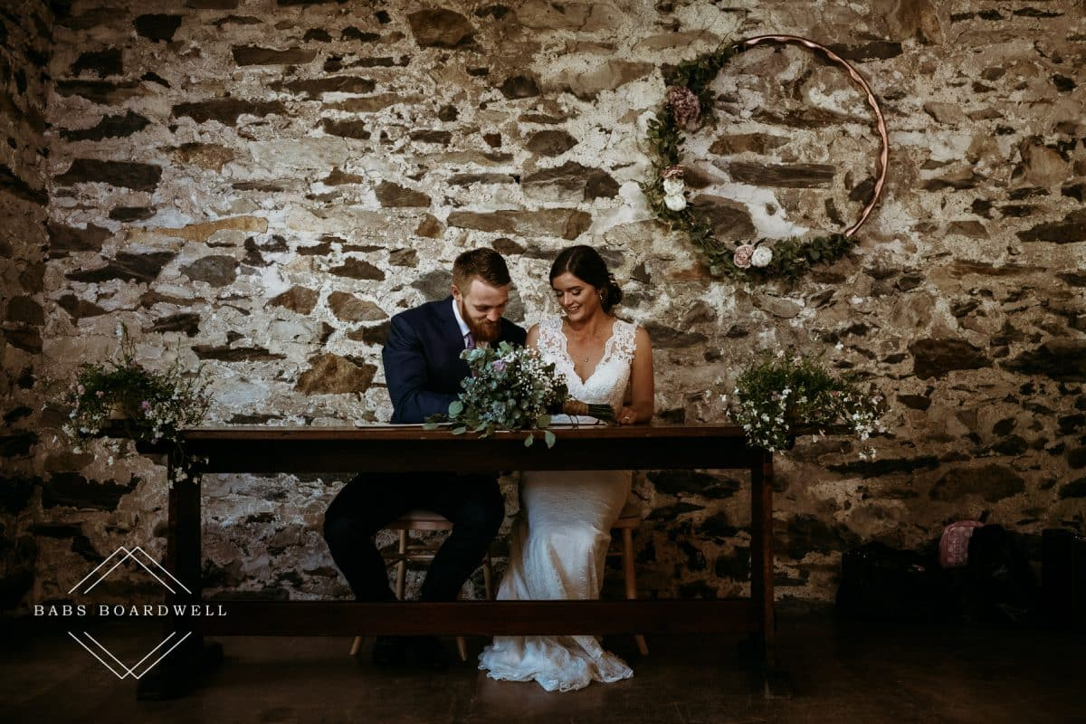 bride and groom signing the register at Llyn Gwynant Barns