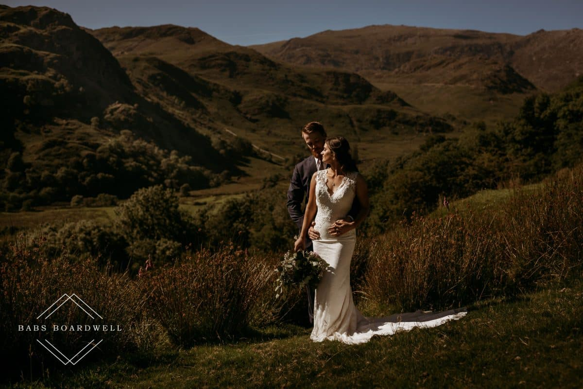 bride and groom standing in a group of mountains