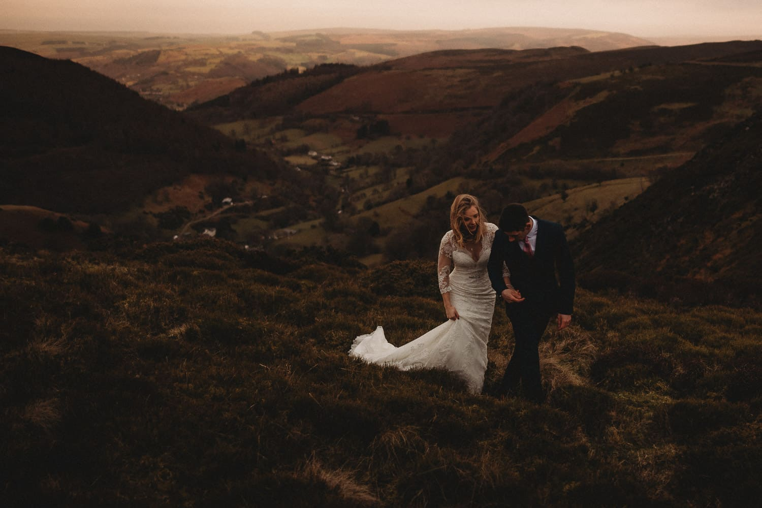North Wales Wedding Photographer couple dressed in wedding dress and suit walking across the heather in the hills above Llangollen