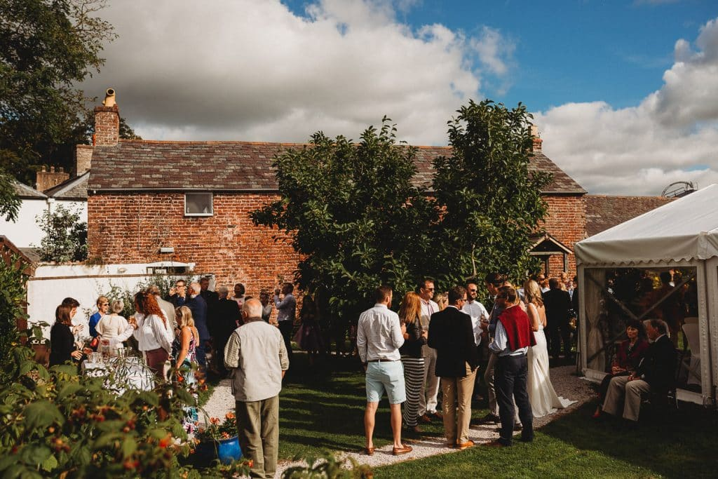 North Wales Wedding Photographer at Pentre Mawr Country House guests mingling in the secret garden at a wedding