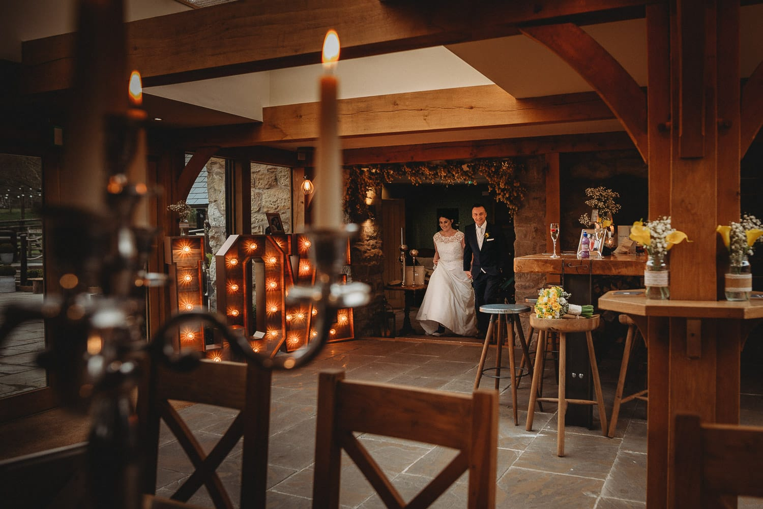 bride and groom making their entrance with candles in the foreground and the love letter on the side at Tower Hill Barns