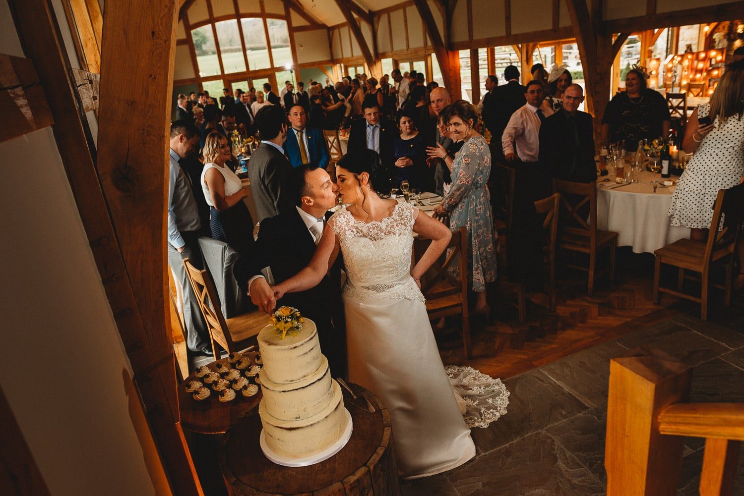 bride and groom kissing while cutting the cake and their wedding guests in the background at Tower Hill Barns