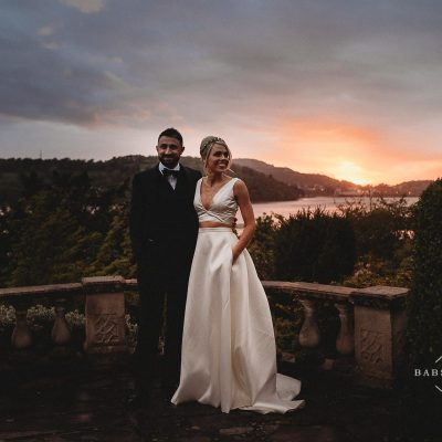 bride wearing 2-piece wedding dress and groom wearing bow tie at sunset