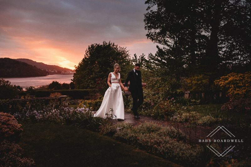 bride and groom walking in the sunset holding hands on their wedding day in Conwy