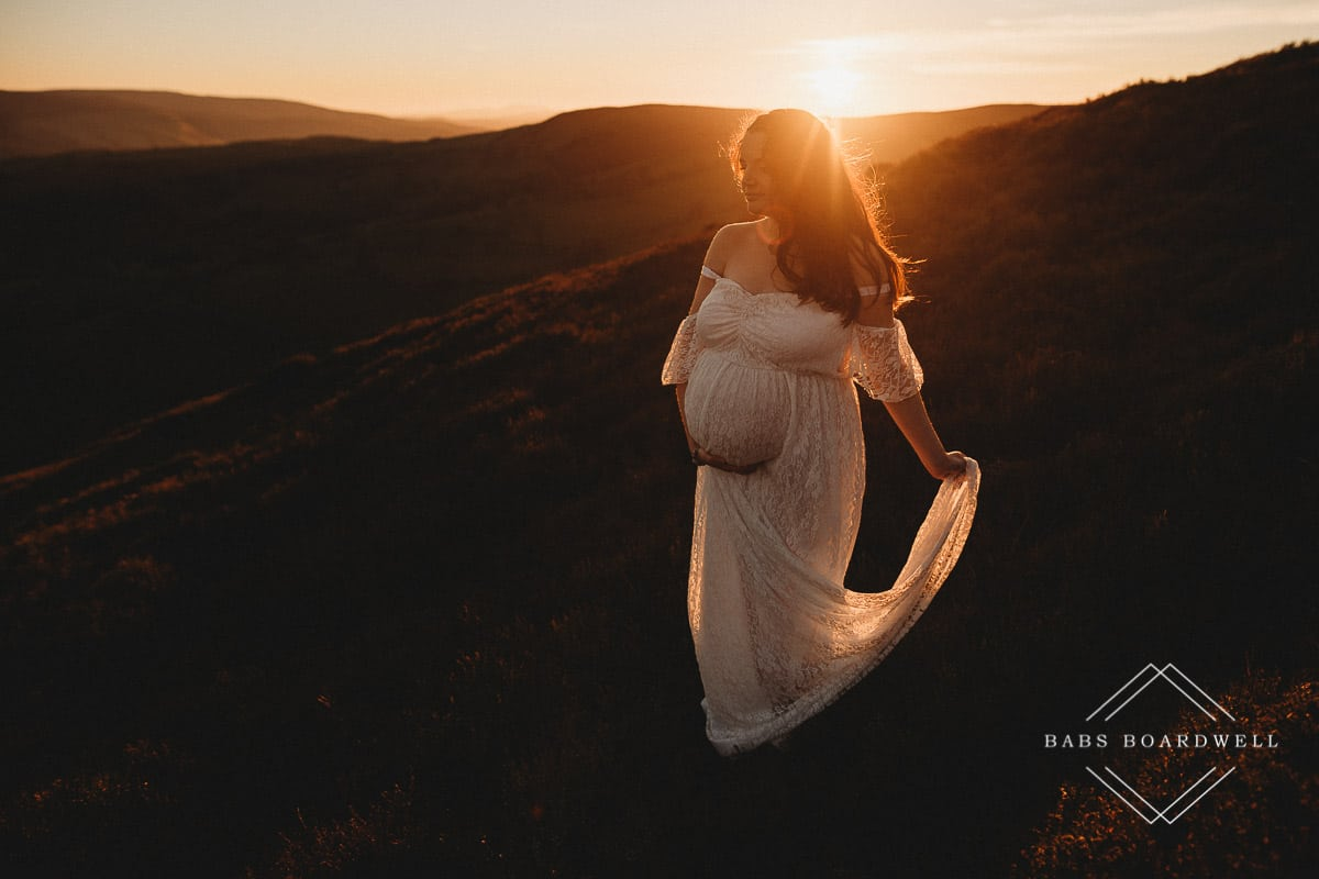 pregnant woman wearing a white dress at sunset