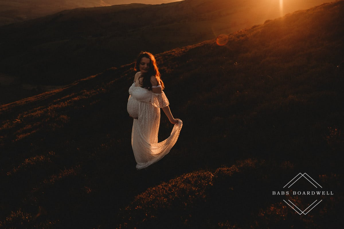 pregnant woman in a white shoulder less dress at sunset