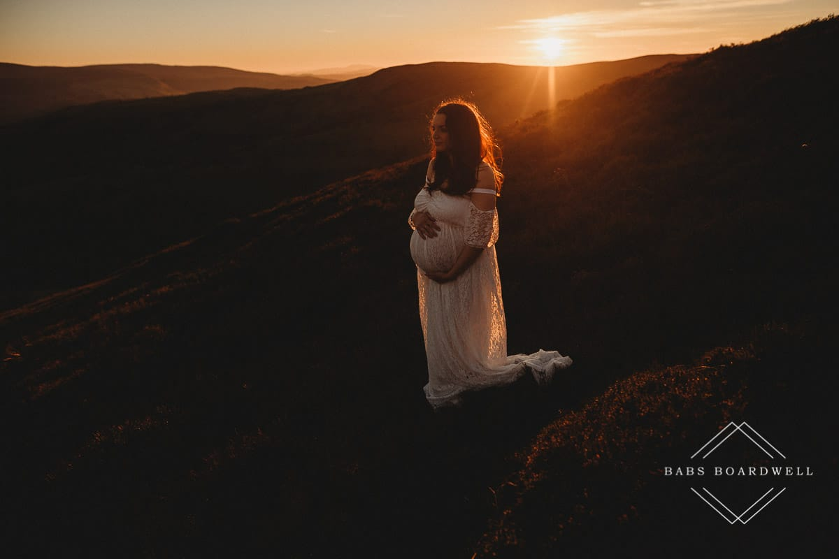 pregnant woman in a white shoulder less dress at sunset by Maternity Photographer in North Wales