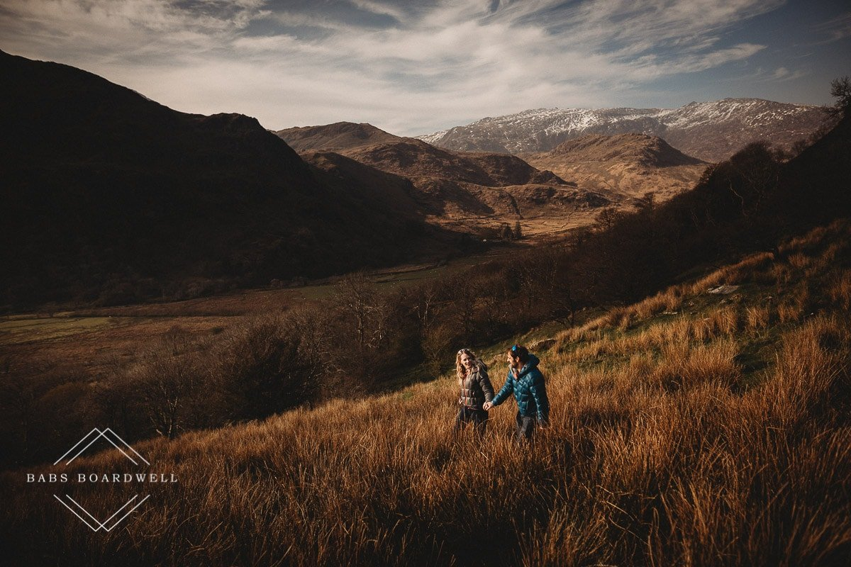 couple walking hand in hand with snow-capped mountains in the background during scenic pre-wedding shoot at the base of Snowdon