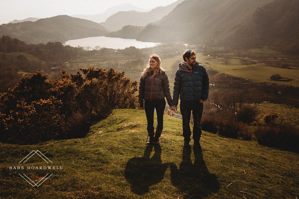 couple standing next to each other with mountains and a lake in the distance during scenic pre-wedding shoot at the base of Snowdon