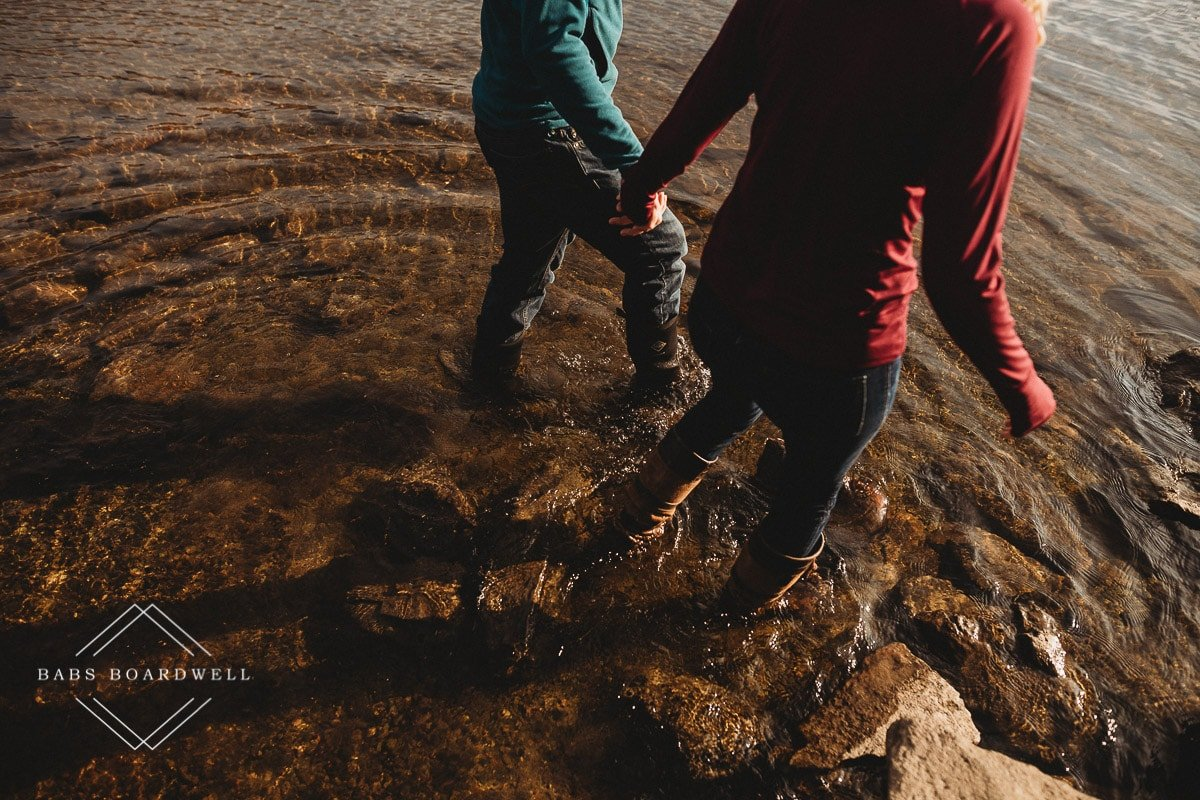 close-up of couple holding hands while walking in shallow water