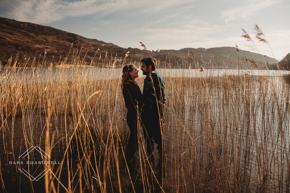 couple standing in the water amongst some plants during scenic pre-wedding shoot at the base of Snowdon