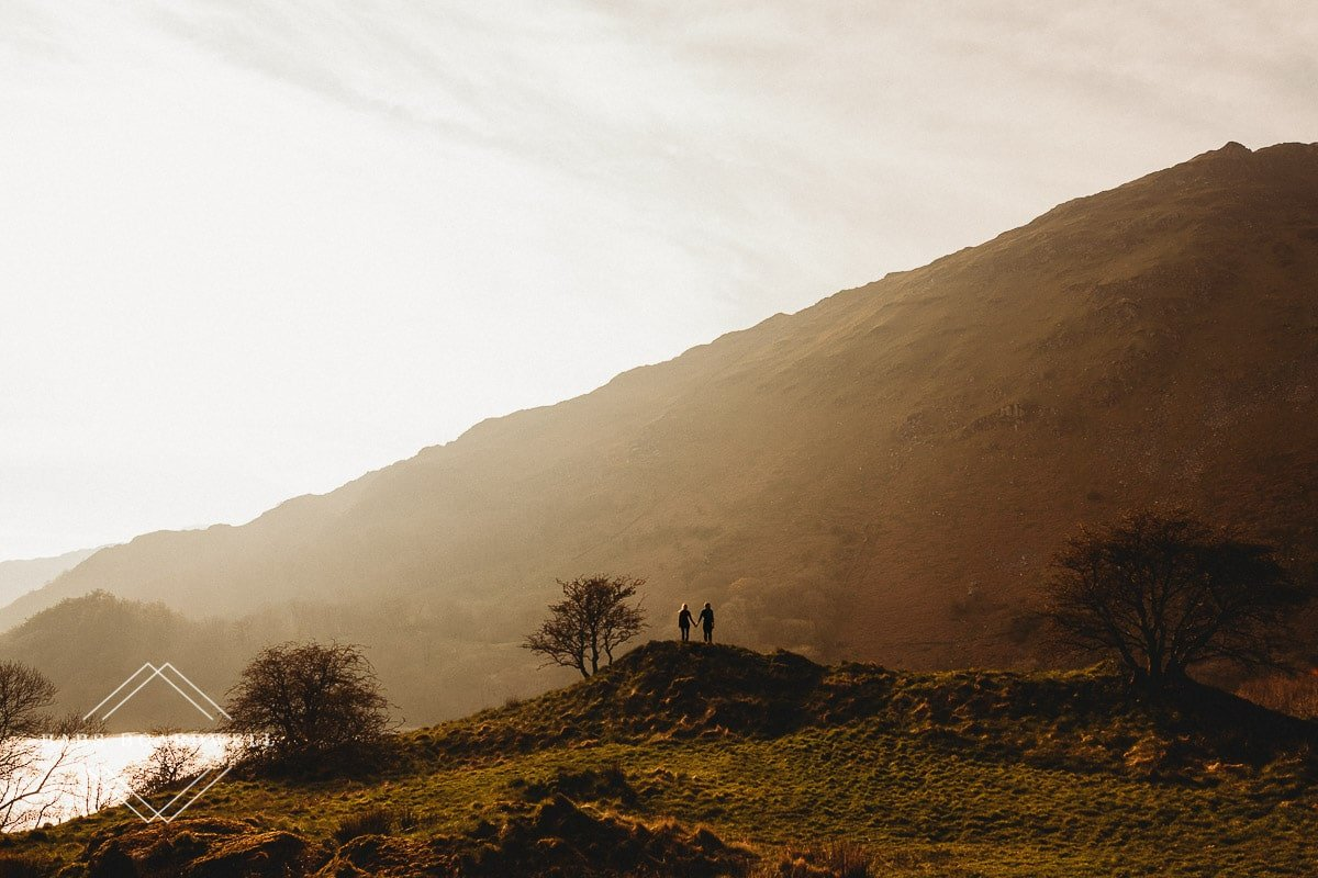 couple standing next to each other while holding hands on a mound at sunset during scenic pre-wedding shoot at the base of Snowdon