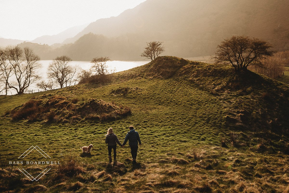 couple walking hand in hand towards a lake with their dog by their side at sunset during scenic pre-wedding shoot at the base of Snowdon