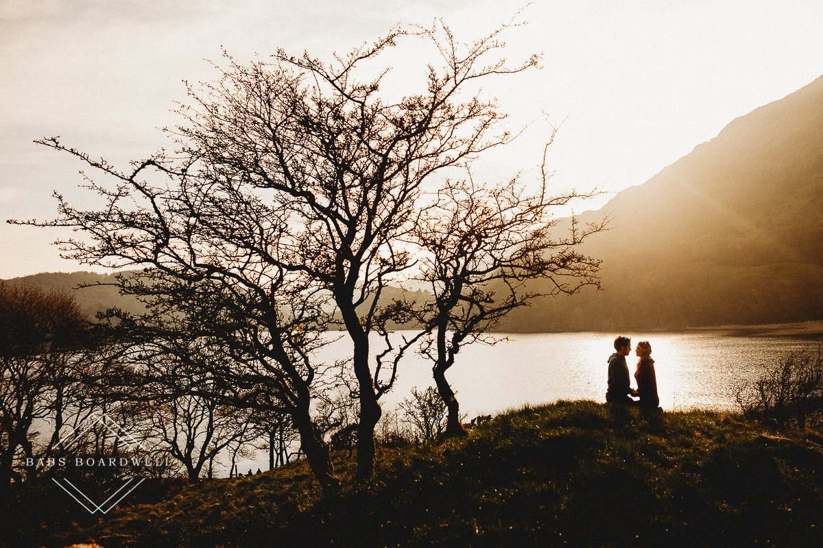 couple sitting opposite each other by a lake during sunset with a tree on the left hand side of the image