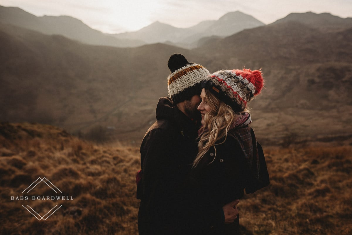 couple hugging wearing knitted bobble hats during scenic pre-wedding shoot at the base of Snowdon
