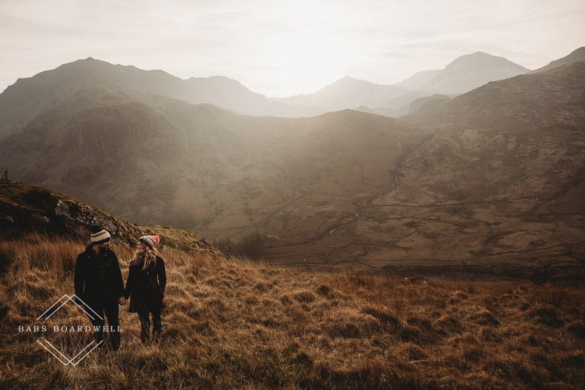 couple standing next to each other while holding hands wearing knitted bobble hats during scenic pre-wedding shoot at the base of Snowdon