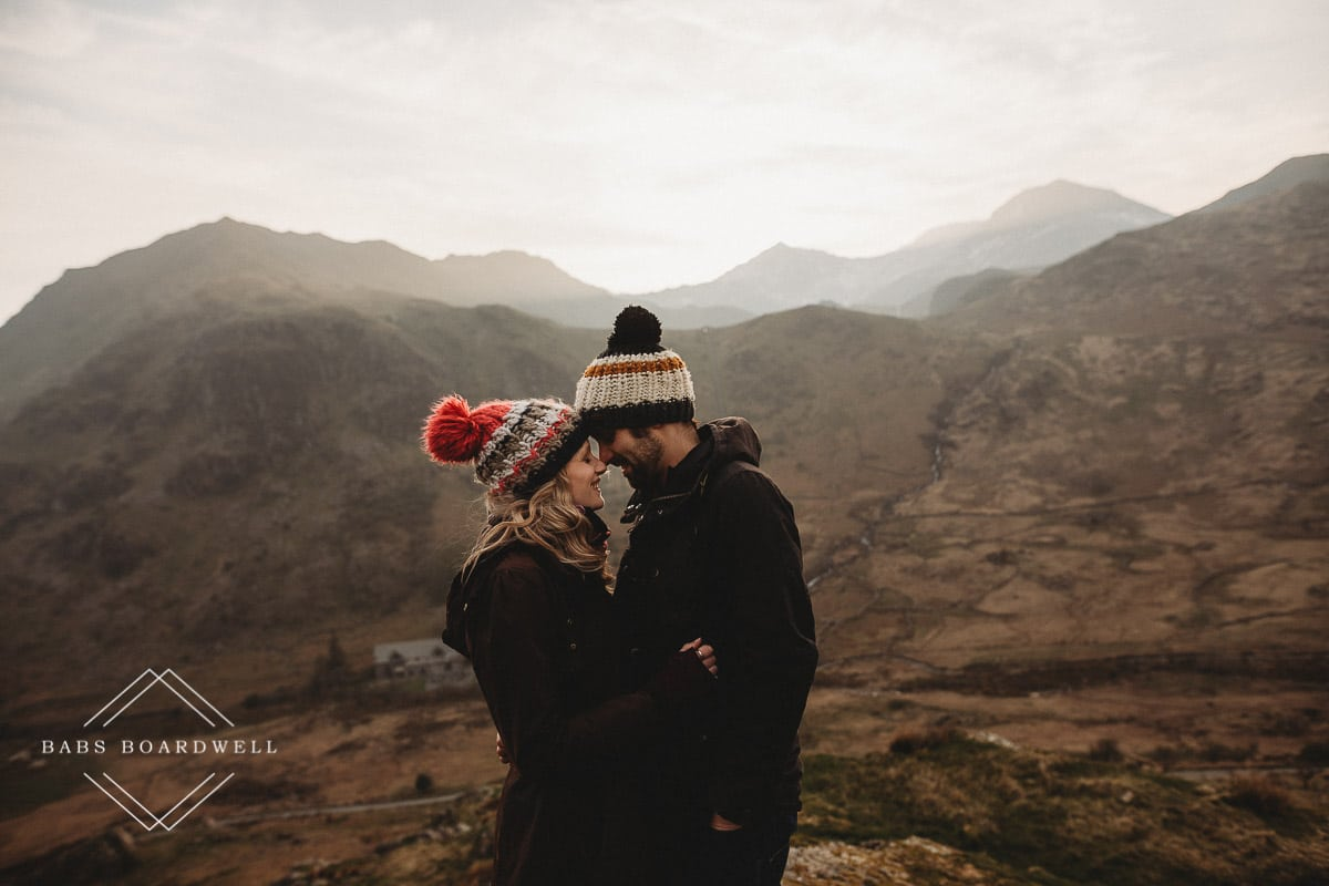 couple hugging wearing knitted bobble hats