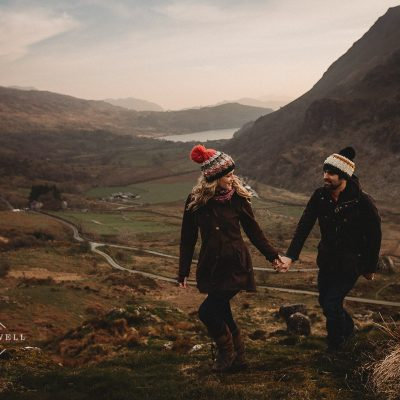 couple walking hand in hand wearing knitted bobble hats with a lake and mountains in the background during scenic pre-wedding shoot at the base of Snowdon