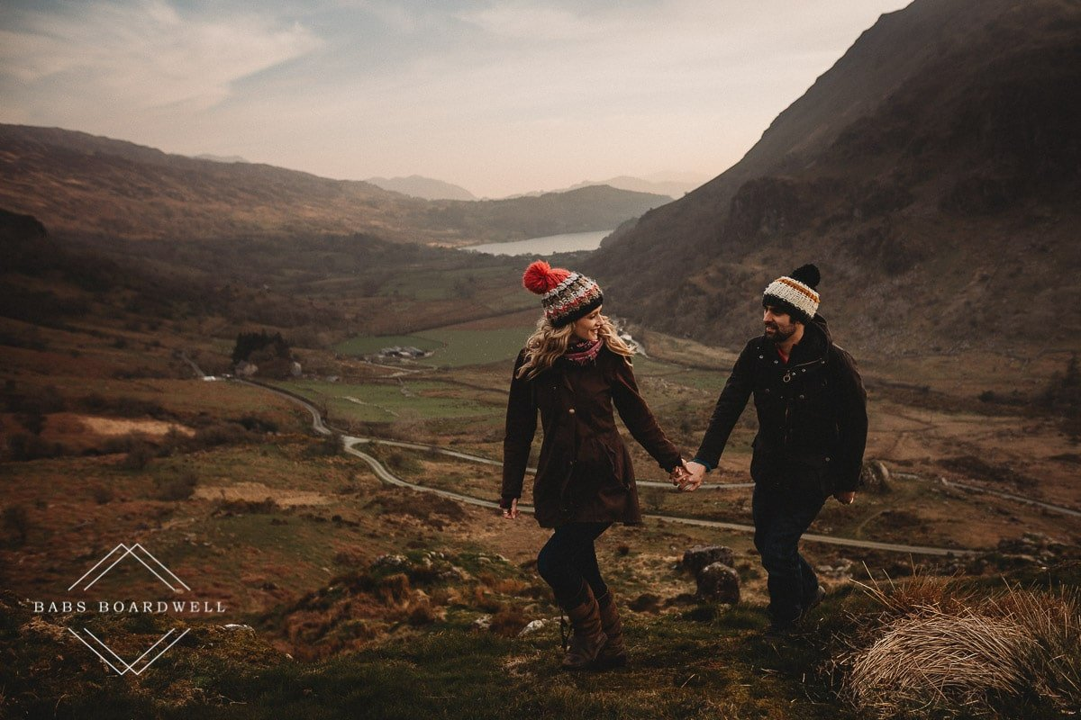 couple walking while holding hands wearing knitted bobble hats during scenic pre-wedding shoot at the base of Snowdon