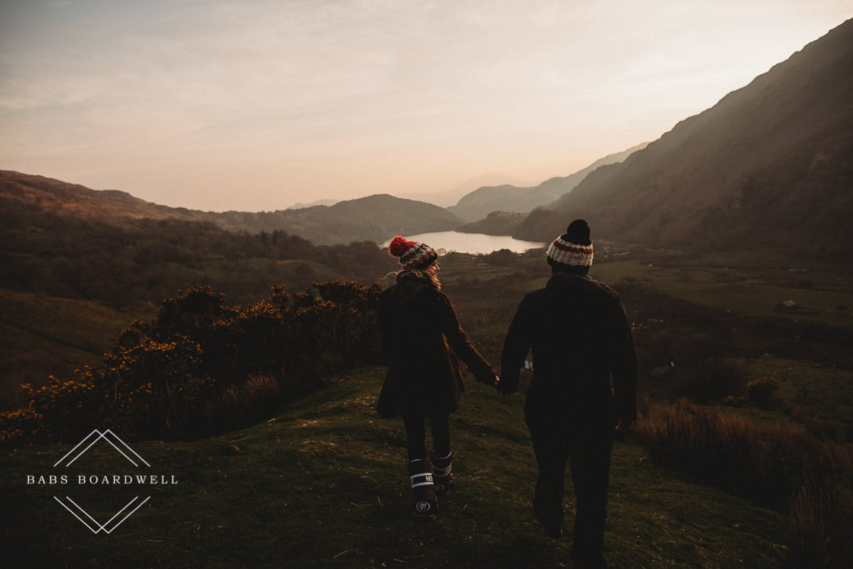 couple walking hand in hand wearing knitted bobble hats and moon boots at sunset with a lake and mountains in the background