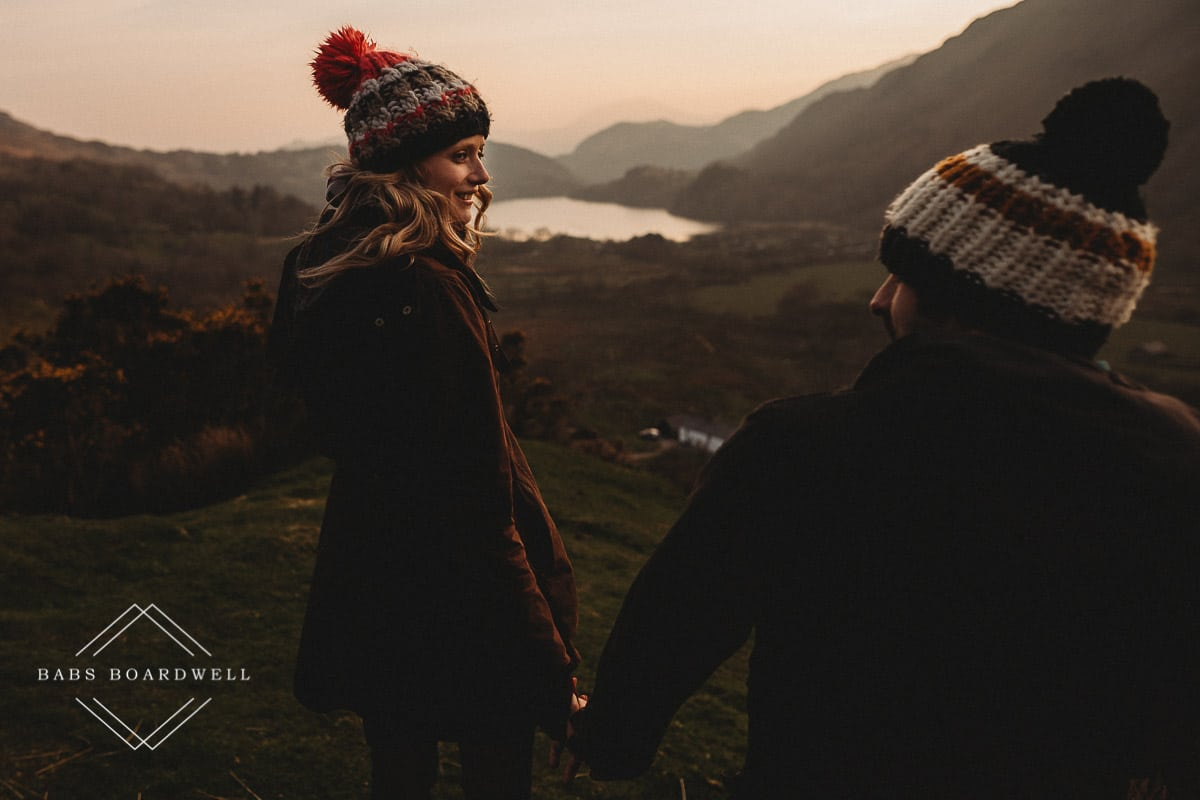 couple walking hand in hand wearing knitted bobble hats at sunset with a lake and mountains in the background